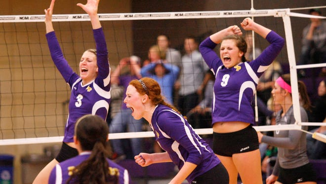 University of Wisconsin-Stevens Point setter Alexis Hartman (center) celebrates with teammates Allison Davis (3), Bri Piepenbrok (2) and Gabby Thomas (9) after the Pointers upset No. 4 ranked St. Thomas in St. Paul, Minn.