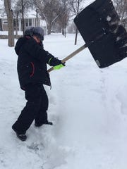 Keason Ketchum, 5, helps his grandpa shovel snow in Great Falls. The boy was excited to help, burn off energy and be outside. The snow came down so fast Wednesday many people shoveled the sidewalk over and over.