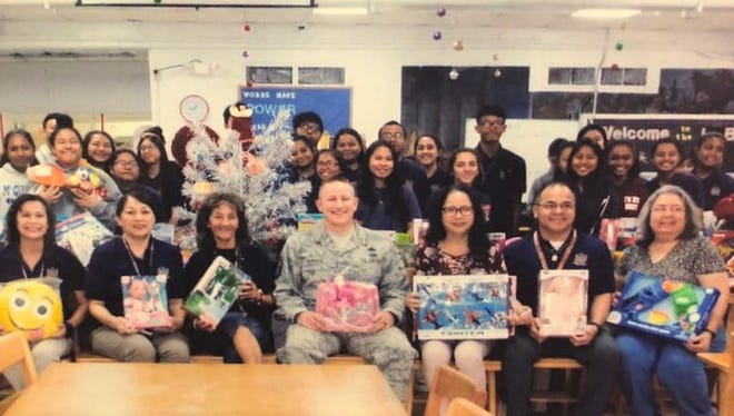 The G.W. High School student of Bernice Babauta, Tina Flores and Rose Unpingco donated toys for the Air Force Christmas drop. Seated from left: Lynda H. Avilla, principal, Molly Aguon, Tina Flores, Master Sergeant, USAF Jarrett Gardner, Bernice Babauta, John Castro, assistant principal and Rose Unpingco, librarian.