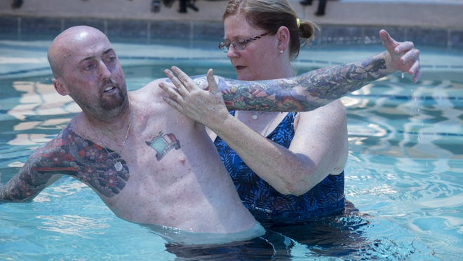 Phoenix Police Officer Ben Denham (left) works with Mary Krurchowshy (physical therapist), June 13, 2016, during aquatic therapy at the Banner Thunderbird Outpatient Treatment Center, 5555 West Thunderbird Road, Glendale, Arizona.