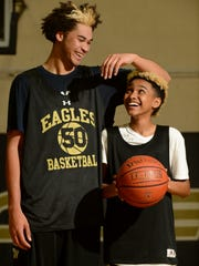Ezekiel Richards, at 6 feet, 11 inches, towers over 5-foot-6 teammate Jacob Gaines as the Oak Park High boys basketball team prepares for a CIF-Southern Section playoff opener Friday at Bishop Montgomery.