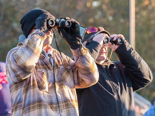 Two men use binoculars to view the Antares rocket at Wallops Flight Facility Visitor's Center on Saturday, Nov. 11, 2017.