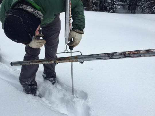 Ian Bardwell weighs a snow sample during a snow survey in the Bob Marshall Wilderness.
