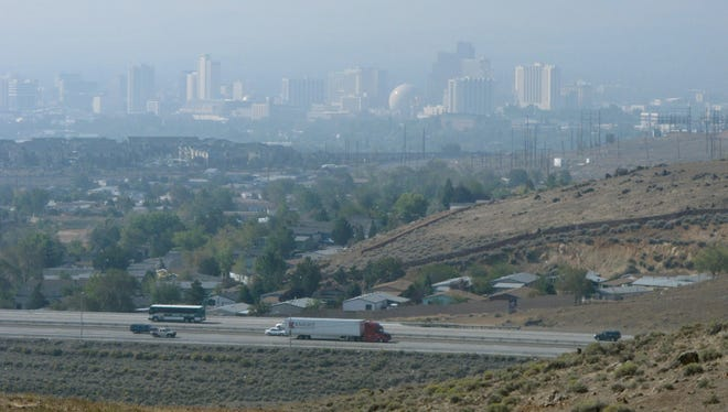 Traffic proceeds on U.S. 395 northeast of downtown Reno on Monday as dense smoke drifts in from a California wildfire more than 60 miles away. The haze obscured the Sierra range just west of the city. It has triggered air quality alerts up and down the Sierra's eastern front for more than a week.