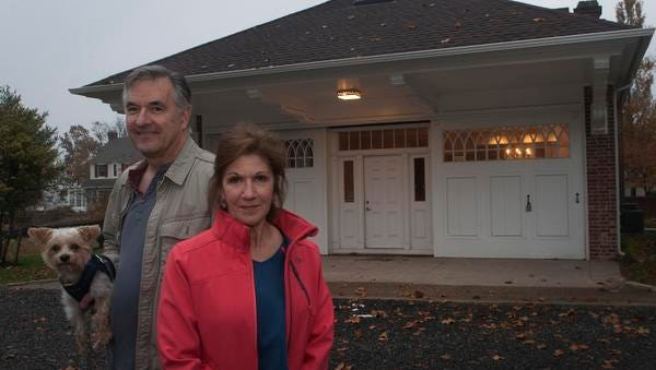 Joseph Barolin and Martha Colameco stand outside their new house with their dog Bigelow.