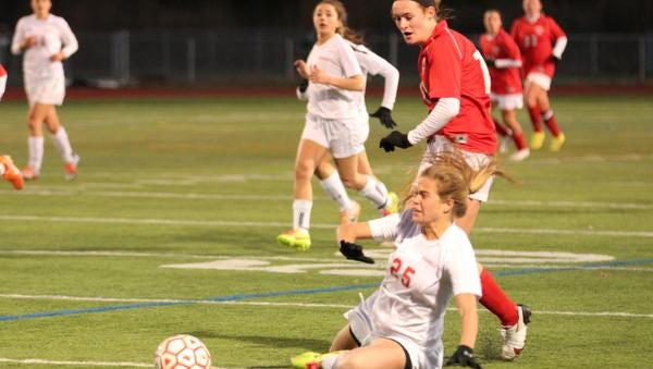 Byram Hills' Abbey Kelin falls in a battle for the ball with Somers' Hannon Eberts during the second half of the Class A final on Sunday.