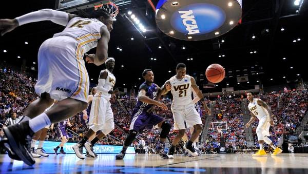 In San Diego, VCU Rams guard Treveon Graham (21) battles for a loose ball with Stephen F. Austin Lumberjacks guard Desmond Haymon during a men's college basketball game Friday during the second round of the 2014 NCAA Tournament at Viejas Arena.