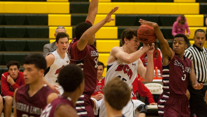 Dontae Aguirre (3) of the Sierra Linda Bulldogs blocks a pass from the Scottsdale Christian Eagles in the first half of their game during the Horizon Holiday Holiday Hoops Tournament Friday Dec. 19, 2014 in Scottsdale.
