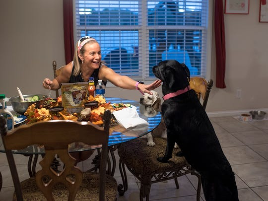 "Elizabeth Morgan stops Bella, her dog and running partner, from chowing down at her home on Thursday, Oct. 19, 2017. Morgan adopted Bella two years ago, and the two have run six half-marathons together. ""We saved each others' lives, really,"" said Morgan. Bella would have been euthanized because of her high energy if she had not been adopted."