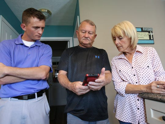 (L-R)  Aaron Cooley, 33, and his parents Karl Cooley and Brenda Cooley listen to audio of Aaron's brother and their son Adam who died of a drug overdose.  Karl has the audio recording on his smartphone.