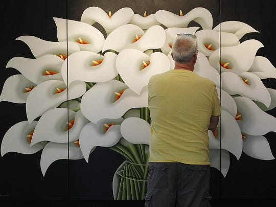Tom Brassell, an artist from Chicago, checks out a detail in a painting by artist Michael Kuseske, from Royal Palm, Fla, at the Lakefront Festival of Art at the Milwaukee Art Museum in 2017.