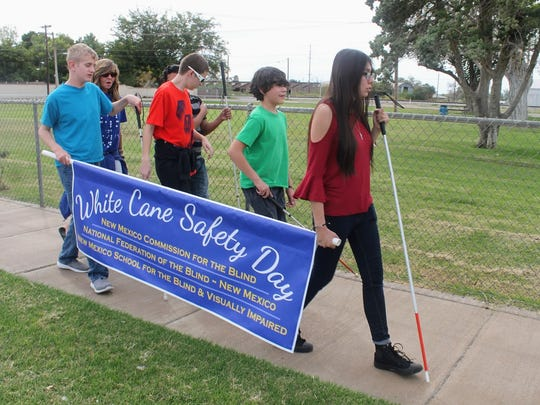 Students from the New Mexico School for the Blind and Visually Impaired walk down White Sands Boulevard holding up a White Cane Safety Day Banner to raise awareness for motorists to be vigilant of visually impaired people using public streets.