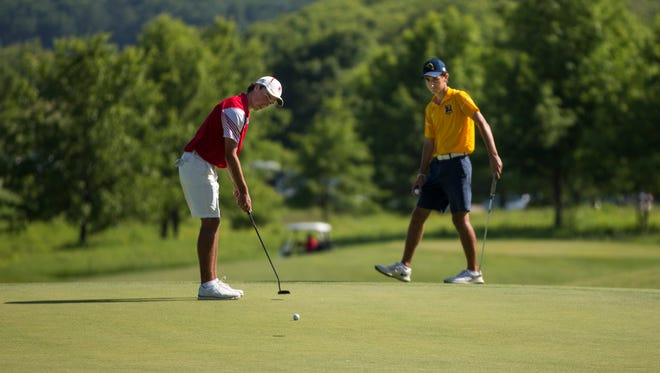 Arrowhead's Piercen Hunt putts on the ninth as  Marquette's Andrew Sagrillo looks on.