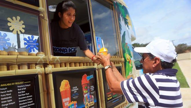 Antonio Salazar receives a free snow cone from Katrina Maldonado from Kona Ice.as Reliant Energy opens its annual Beat the Heat Center on Wednesday, May 31, 2017, in Corpus Christi.