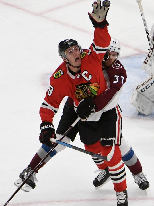 Chicago Blackhawks center Jonathan Toews (19) reaches for the puck next to Colorado Avalanche center Tyson Jost (17) during the second period of an NHL hockey game Tuesday, March 20, 2018, in Chicago. (AP Photo/David Banks)