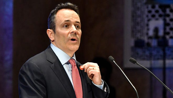 Kentucky Governor Matt Bevin refers to his lapel pin, a pair of scissors, a symbol of his plans to cut spending as he addresses a joint session of the Kentucky legislature during the State of the Commonwealth address, Wednesday, Feb. 8, 2017, in Frankfort, Ky. (AP Photo/Timothy D. Easley)