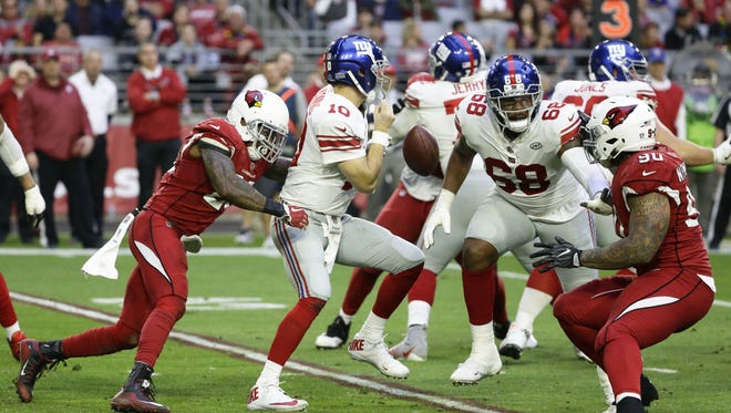 Arizona Cardinals Deone Bucannon forces a fumble from New York Giants quarterback Eli Manning in the second half on Dec. 24, 2017 at University of Phoenix Stadium in Glendale, Ariz. Nkemdiche returned the fumble for a touchdown.