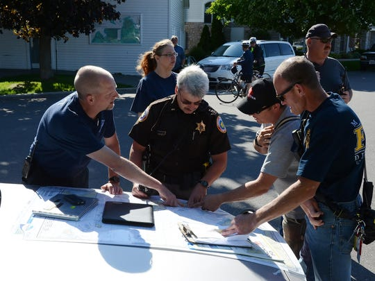 Door County Sheriff's Department officers and fiirefighters look over a map of Green Bay during a kayak rescue Thursday.