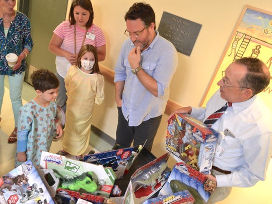 """""""Jurassic World"""" director and co-writer Colin Trevorrow, center, helps Christopher Goldring of Ferrisburgh decide which film-based toy to choose with an assist from Dr. Lewis First, chief of pediatrics at The UVM Children's Hospital. Christopher opted for large dinosaur claws."""