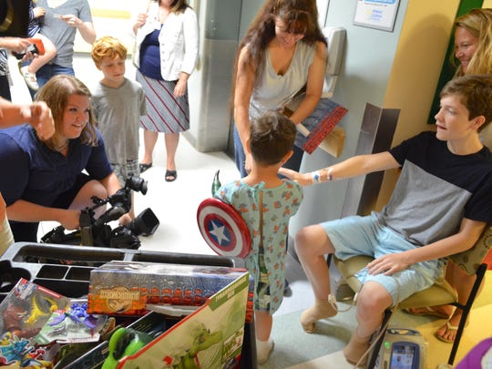 Christopher Goldring of Ferrisburgh, a patient at The University of Vermont Children's Hospital, shows his mother, Leslie, the toy given to him by Colin Trevorrow.