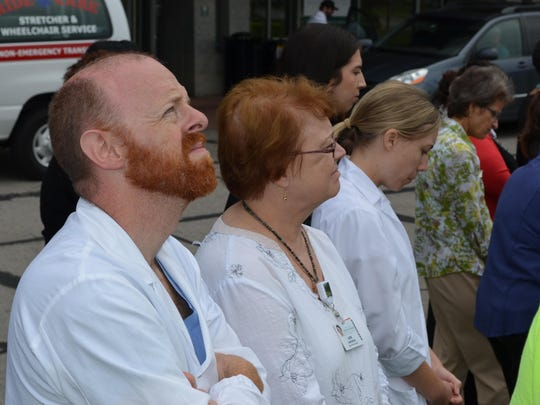 University of Vermont Medical Center clinical staff members listen as a prayer is read at the ceremony.
