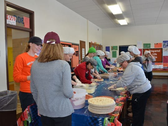 """The original Marshfield Middle School Home Economics rooms were turned into a """"Power of Pizza"""" parlor on Feb. 11. Middle School staff and students raised money for the FACS program. Forward Financial Bank, represented by Holly Zopfi, teamed up with """"The Power of Pizza"""" and Bents Chiropractic Center to assist with the fundraiser. Zopfi recently presented a check to Samantha Will (Marshfield Middle School)."""