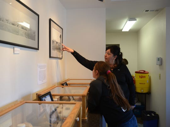 Theresa Coffman points to an old photo of the Reno-Sparks Indian Colony for her daughter, Jayci, 11, during the opening of the new cultural center. The center, formerly known as the Field Matron's Cottage, will show a display of pipes, handmade by local centenarian Hilman Tobey, and other artwork and historical items for a week.