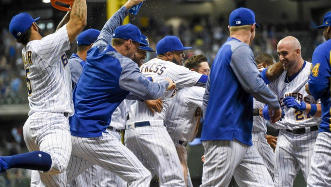 Travis Shaw (right) is mobbed by his teammates after his bases-loaded walk with two outs in the bottom of the 10th inning sent the Brewers to a 4-3 win over the Mets on Friday night at Miller Park.