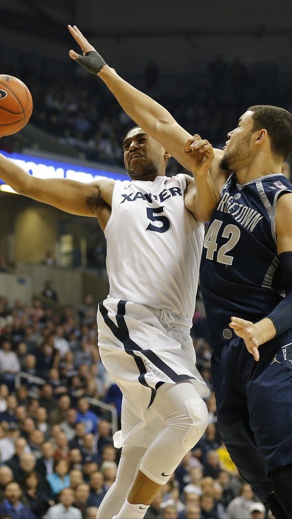 Xavier Musketeers guard Trevon Bluiett (5) is fouled by Georgetown Hoyas center Bradley Hayes (42) as he shoots a layup in the first half of the NCAA mens basketball game between the Xavier Musketeers and the Georgetown Hoyas at the Cintas Center on the campus of Xavier University in Cincinnati on  Tuesday, Jan. 19, 2016. At the half, Xavier trailed the Hoyas 36-31.