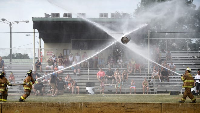Cleona firefighters do battle against Hershey during the Barrel Bust, a fan favorite at the 2016 Lebanon Area Fair Competition Sunday, July 24. Two teams positioned opposite each other move a barrel toward the competition using a stream of water from the fire hose.