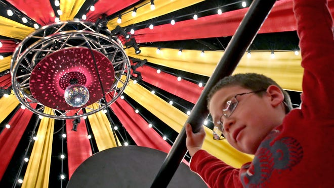 """Jase Zischke hoists bar bells as a strong man at the new """"Circus -- Starring YOU!"""" exhibit at the Children's Museum of Indianapolis."""