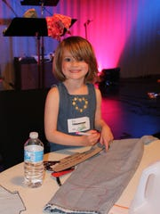 Erin Noonan, 4, of Lewes, helps trace patterns for the shoes.