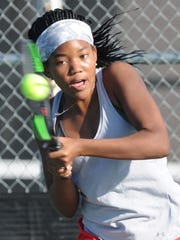 Cooper's Taja Lawrence returns a shot in a match March 3 against Midland High's Allison Stewart. On Monday, Lawrence signed to play with Dallas Baptist.