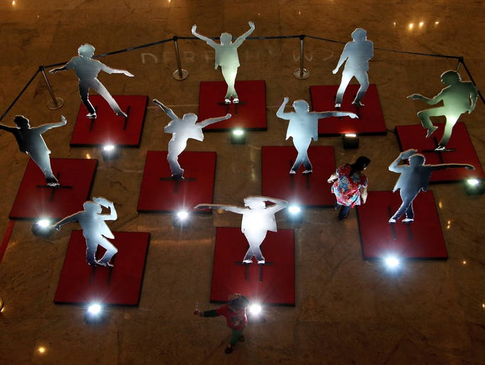 An Indian girl navigates her way though cut-outs of pop star Michael Jackson displayed at a shopping mall on the eve of his birth anniversary, in Bangalore, India, Thursday, Aug. 28, 2014. (AP Photo/Aijaz Rahi)