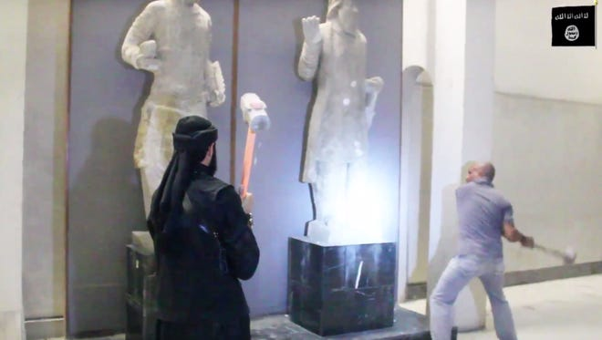 In this image made from video posted on a social media account affiliated with the Islamic State group on Feb. 26, 2015, militants attack ancient artifacts with sledgehammers in the Ninevah Museum in Mosul, Iraq.