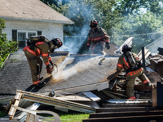 Evansville firefighters tear apart the remains of a