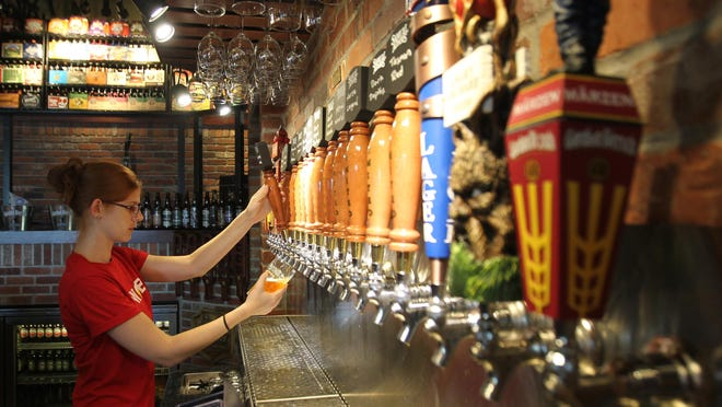 World of Beer bartender Meagan Mason pulls a Samuel Adams Grumpy Monk draft at the Bell Tower Shops location. World of Beer has a special offer for teachers on Teacher Appreciation Day.