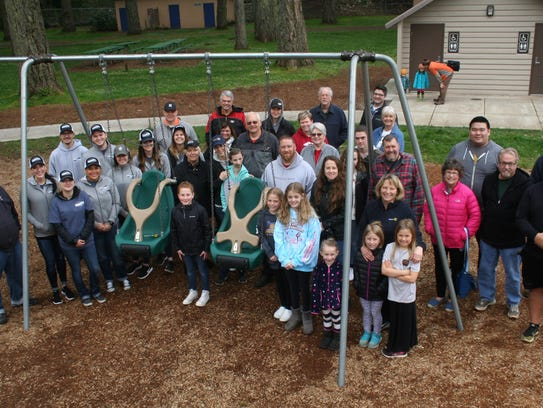 """Rotary members and volunteers pose for a photo at the installation of """"adaptive"""" swings at Coolidge McClain Park in Silverton."""