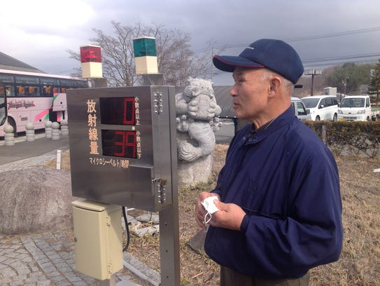 Volunteer Muneo Kanno stands near a radiation meter