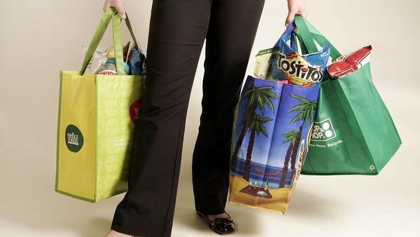 A variety of reusable shopping bags available for sale at grocery stores. State legislation would encourage shoppers to use bags like these instead of plastic.