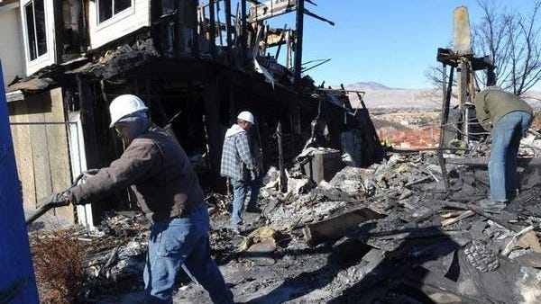 Workers including Sean Lyon, left, clear Thursday a home on Starr Meadows Loop destroyed in the Caughlin Fire on Nov. 18, 2011.