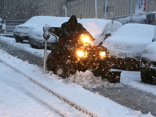 A worker clears the sidewalk in front of Yonkers Honda on Yonkers Ave. in Yonkers, Feb. 5, 2016.