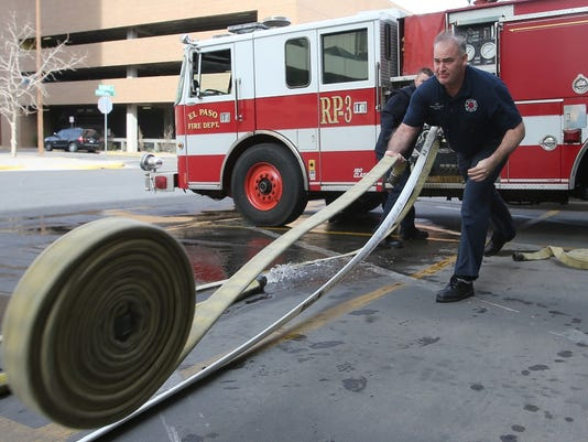 Fire Suppression Technician Shane Haggerty rolls out a section of hose to be tested Monday at the central fire station.
