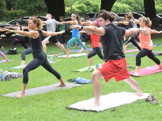 ANI Yoga Julie Lavergne (left) and Chris Bellino stand in a warrior pose. Central Louisiana residents join with thousands of others around the world to practice yoga at the Big Island near Bringhurst Field on International Yoga Day held Sunday morning, Jun