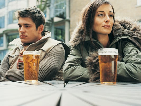 Unhappy Man and Woman Sitting Outside a Pub