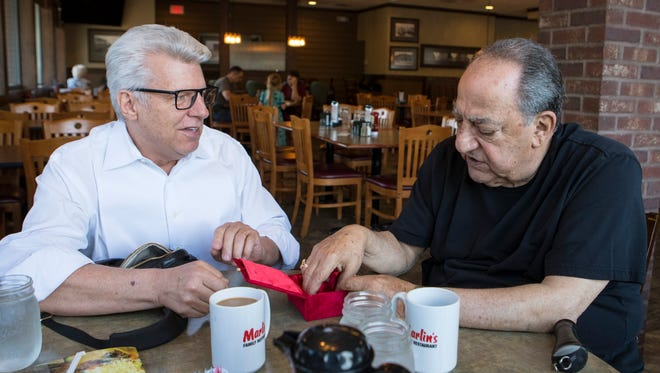 Gene Adballah, former Minnehaha deputy sheriff, looks at his badge which was returned to him by Duke Tufty during a surprise visit at Marlin's Family Restaurant in Sioux Falls, S.D. on Thursday, May 17, 2018. Tufty is now a clergyman in Kansas City.