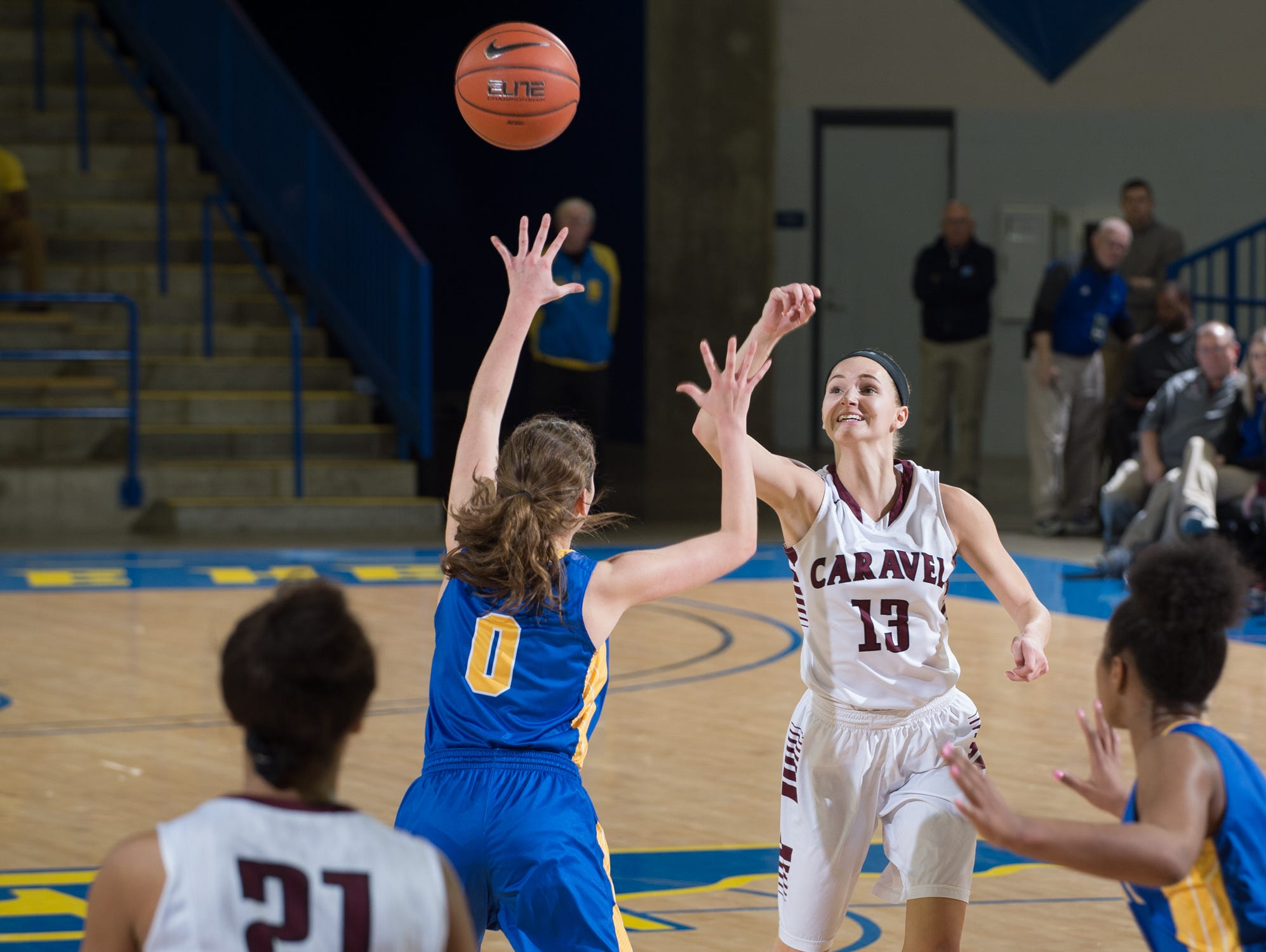 Caravel's Grace Lange (13) passes the ball over A.I. duPont's Adeline Runco (0) in the quarterfinals of DIAA Girls Basketball Tournament at the University of Delaware.