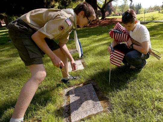 Boy Scout''s Ethan Mawson, 13, (left) and Connor McGraw, 14, both of Troop 1541, place flags on the graves of Veterans in honor of Memorial Day at Forest Lawn Cemetery in Bremerton on Thursday. May, 25, 2017.