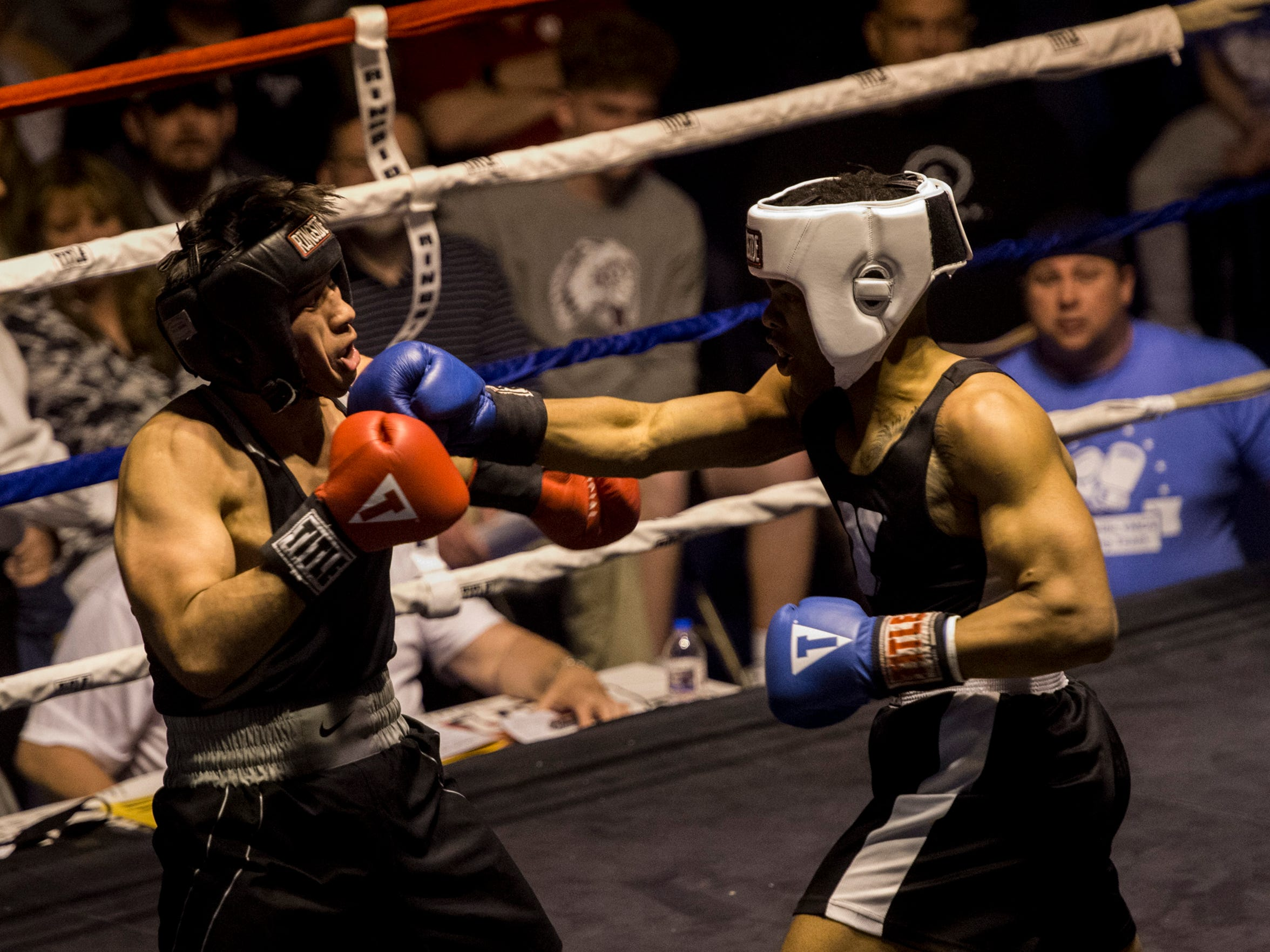 Raymon Henry punches Yorman Guerrero Moctezuma during the Indiana State Golden Gloves championship at the Tyndall Armory in Indianapolis on Thursday, April 26, 2018. Henry fighting through a torn back muscle injury lost the fight but advanced to the national tournament because Moctezuma was unable to go.