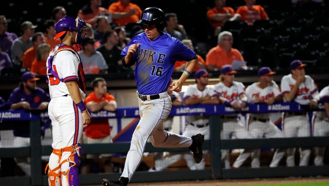 Duke outfielder Michael Smiciklas (16) leaps to touch home plate to score during game 3 of the 2017 ACC Baseball Tournament in Louisville, Ky., on Tuesday.